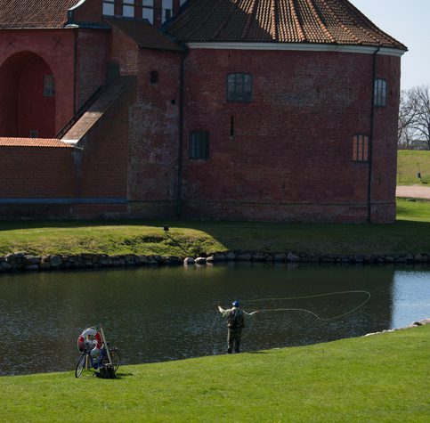 Landskrona, Sweden- May 1, 2013: Fisherman engaged in fly fishing on the  500 years old water that is  surrounding Citadel-fort from 1549. Fly fishing is a very popular sport in Sweden.
